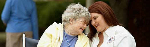 Image of elderly lady laughing with female Comfort Keeper worker