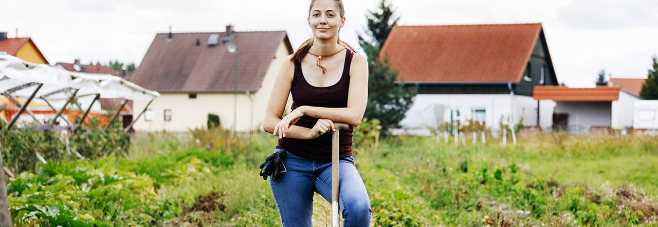 Woman standing in a field with one foot on a garden fork